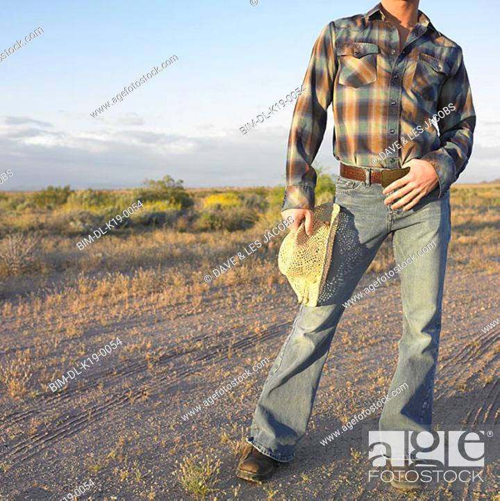 Stock Photo: Low section of cowboy standing outdoors.
