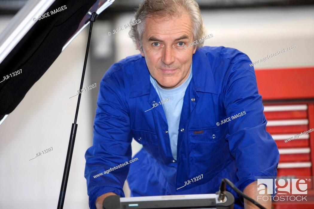 Stock Photo: Mechanic with diagnostic computer by car with open bonnet, portrait.
