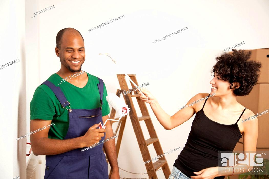 Stock Photo: A playful couple having fun while painting apartment.