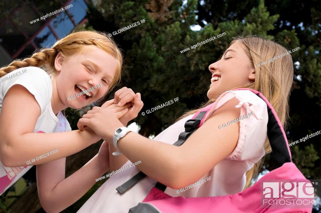 Stock Photo: Low angle view of two schoolgirls playing clapping game and smiling.