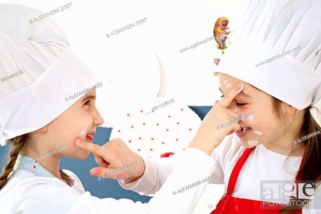Stock Photo: Two little girls with chef's hat kidding around, Munich, Bavaria, Germany.