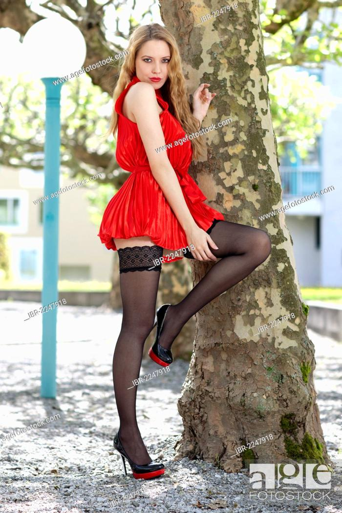 Young Woman Wearing A Red Dress Black Stockings And High Heels