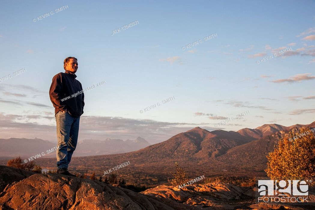 Stock Photo: Man viewing scenery from the top of the Butte, Lazy Mountain in the background on a clear, sunny evening in autumn, South-central Alaska; Palmer, Alaska.