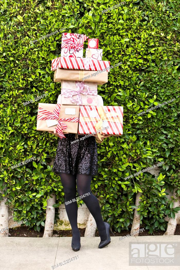 Stock Photo: Caucasian woman carrying Christmas gifts.