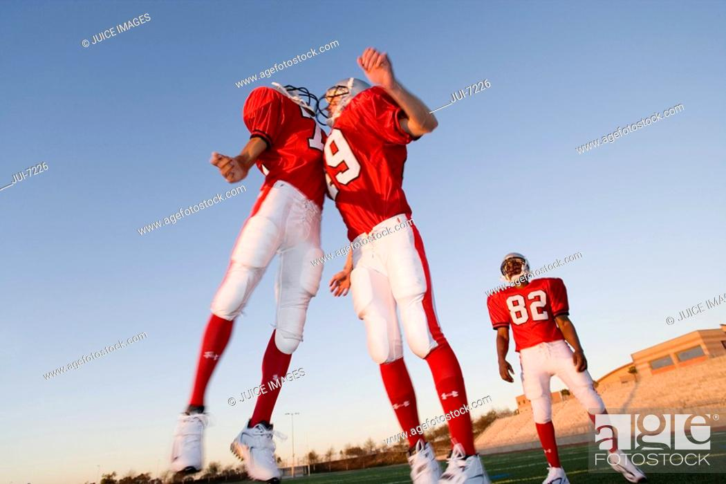 Stock Photo: Two American football players, in red football strips, celebrating touchdown on pitch at sunset, jumping chest to chest, teammate looking on.