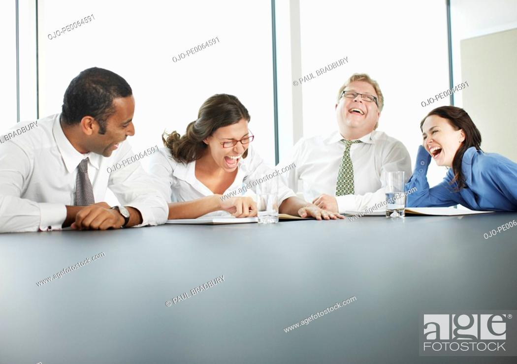 Stock Photo: Businesspeople laughing in conference room.