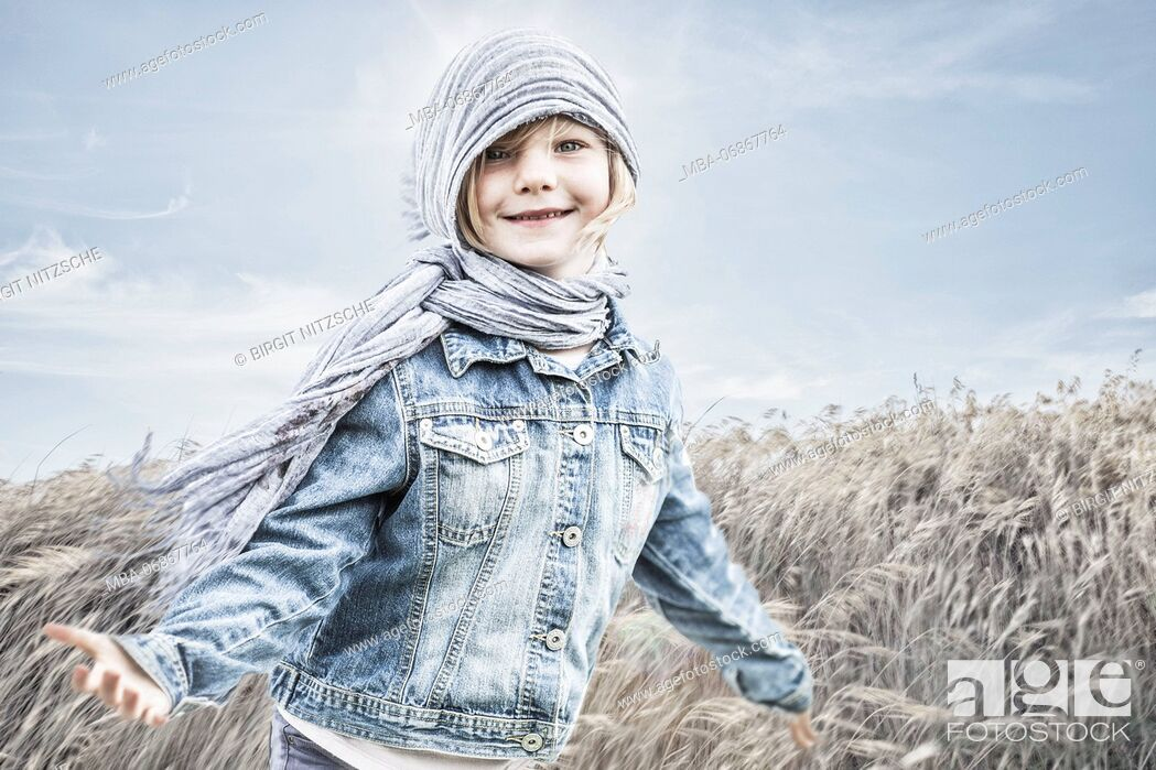 Stock Photo: Little girl standing in a cornfield, against the wind.