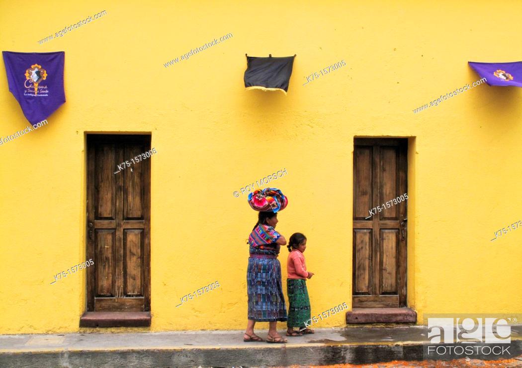 Imagen: Maya mother and daughter walking on cobblestone street during Easter Week.