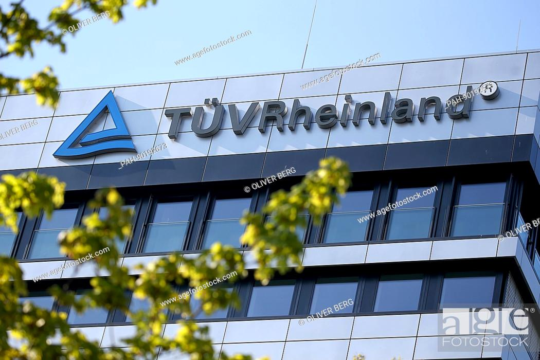 The logo of company TÜV Rheinland hanging up on a building