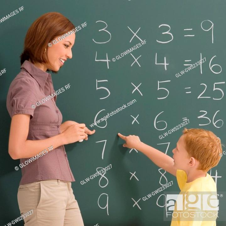 Stock Photo: Side profile of a female teacher teaching her student on a blackboard.