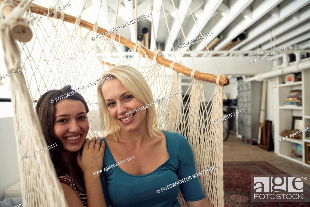 Stock Photo: Portrait of two smiling young women in hammock.