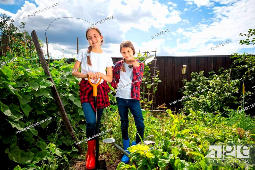 Stock Photo: Two beautiful teenage girls working in garden at sunny day.