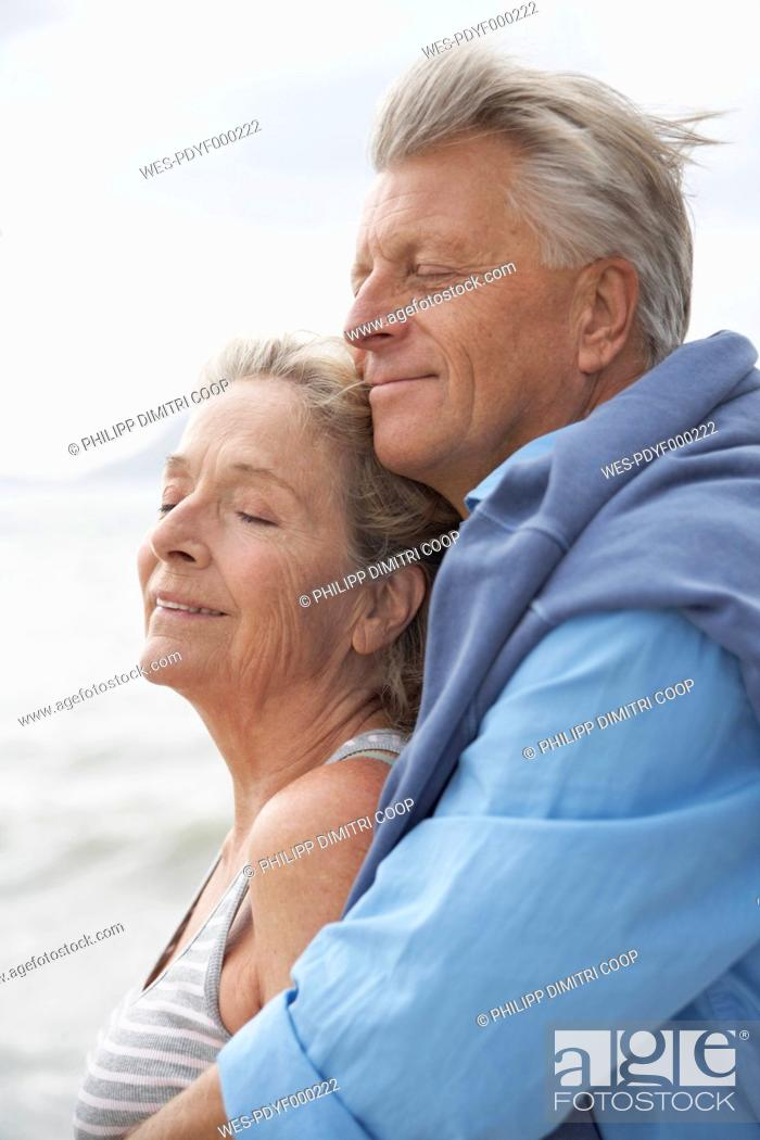 Stock Photo: Spain, Senior couple on beach at Atlantic, smiling.