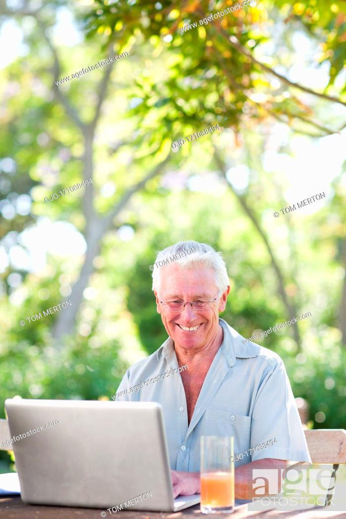 Stock Photo: Senior man using laptop in garden.