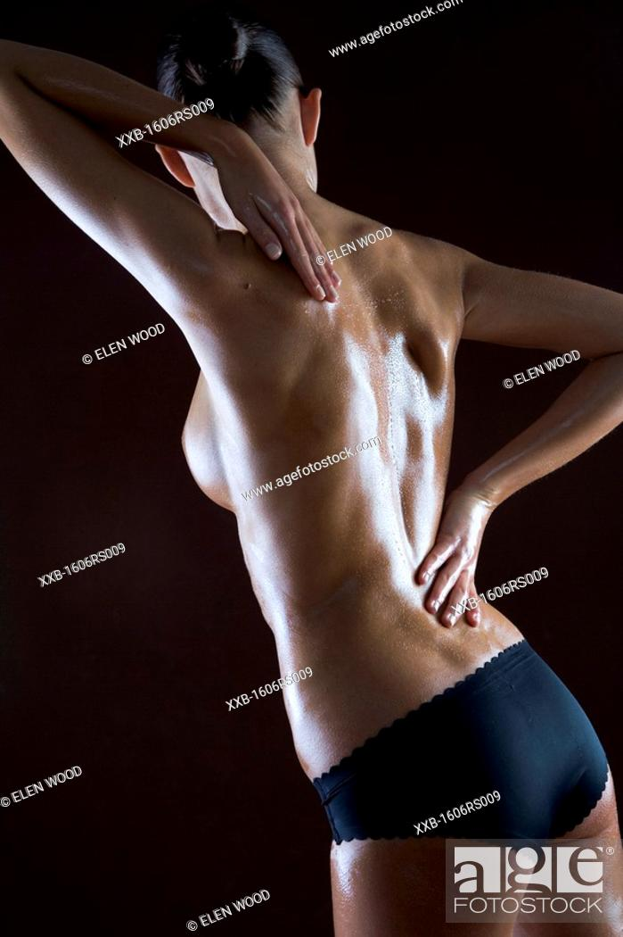 Stock Photo: nude woman putting oil on back.
