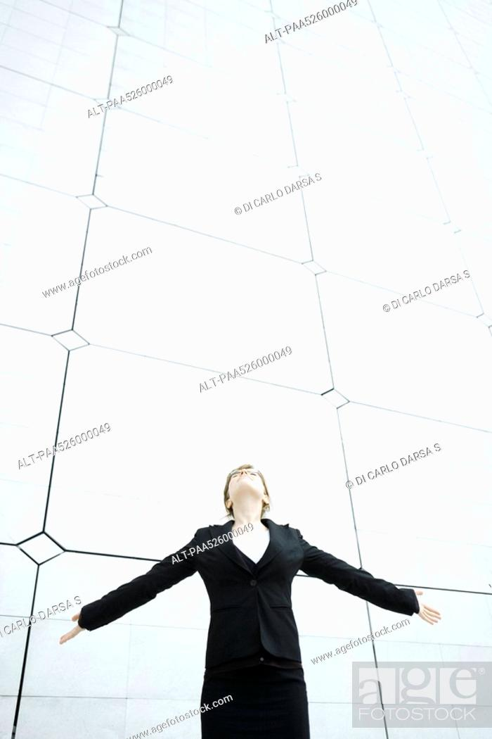 Stock Photo: Woman standing with arms outstretched head back looking up.