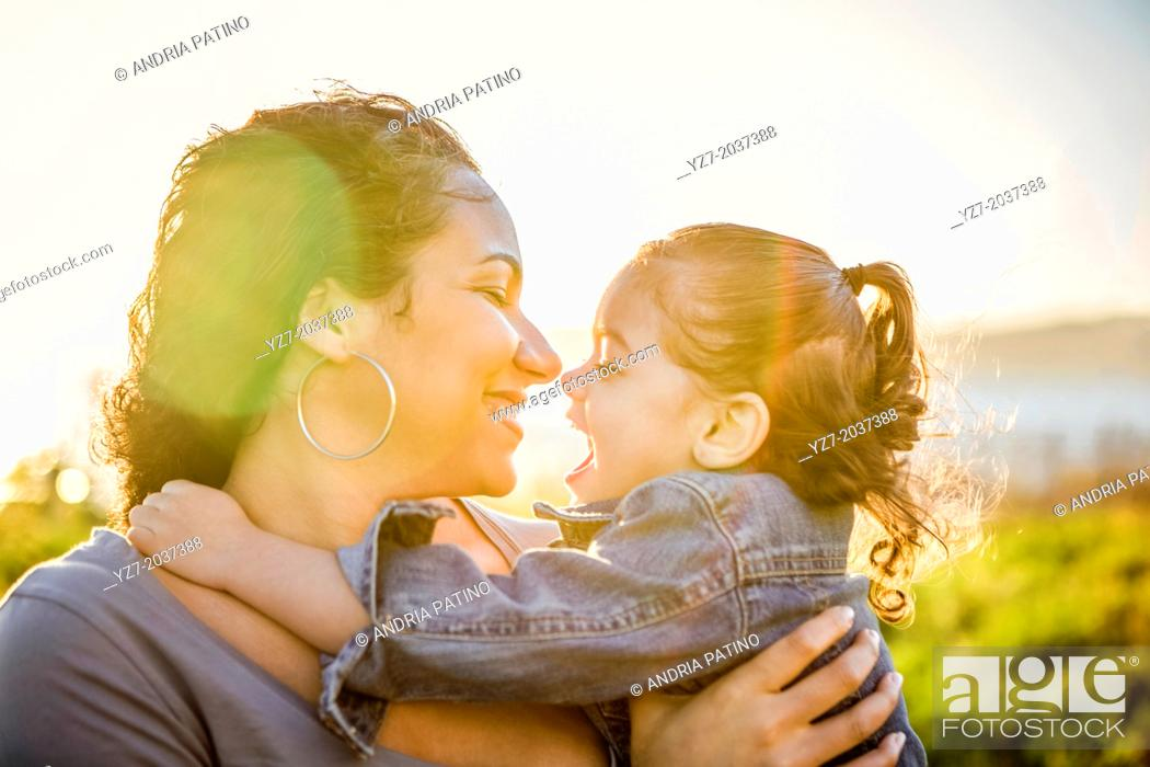 Stock Photo: Mother and daughter embracing with the sun behind them.