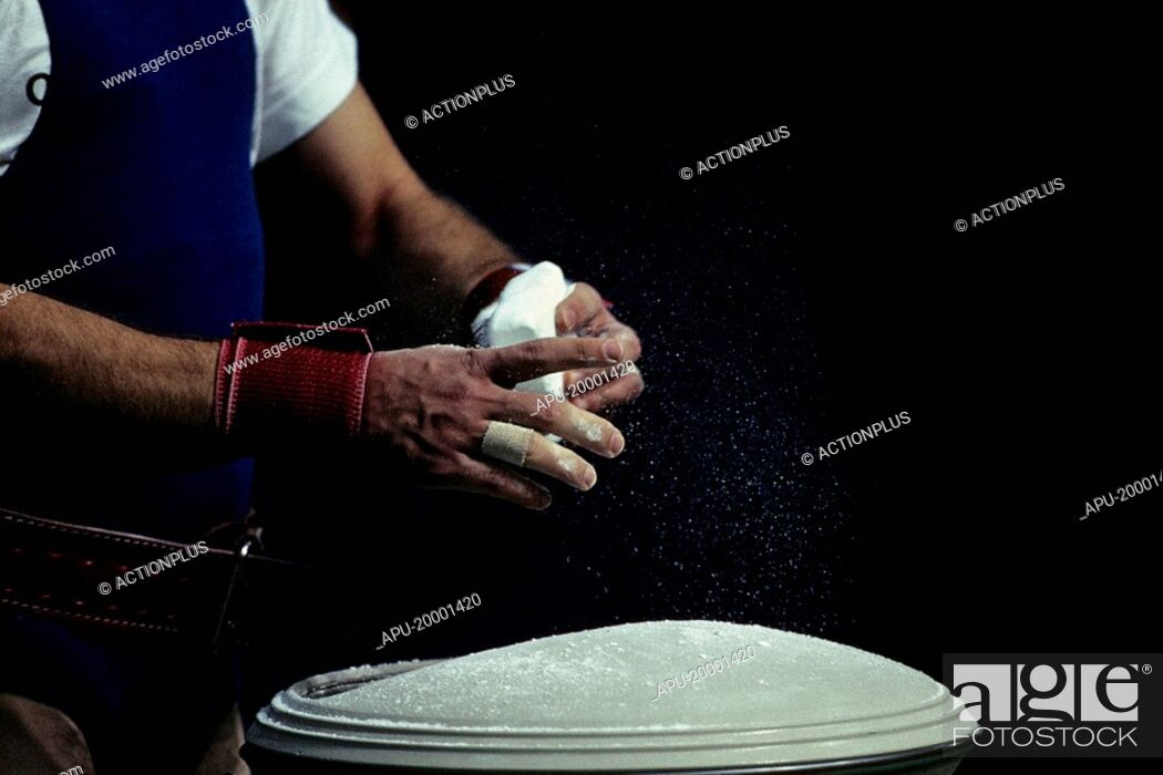 Stock Photo: Weightlifter chalking his hands.