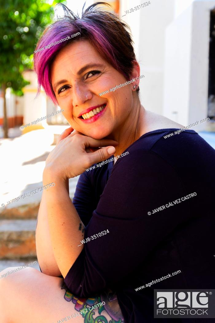 Stock Photo: Portrait color actress happy smiling sitting under trees with coloured tattoos.