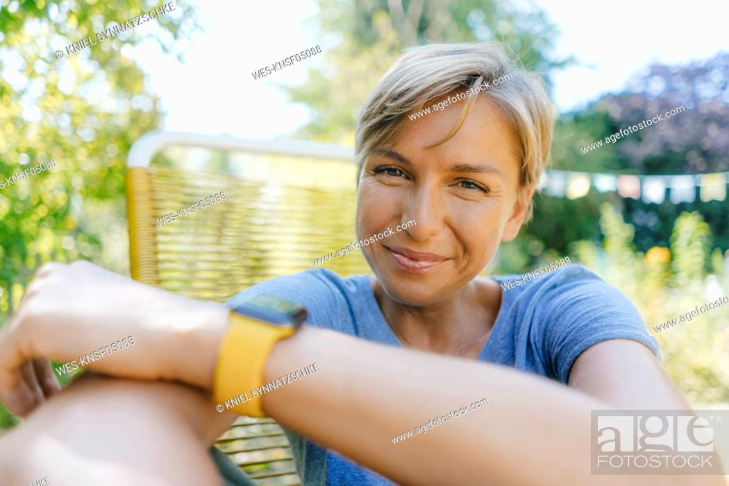 Stock Photo: Portrait of smiling woman sitting in garden on chair.