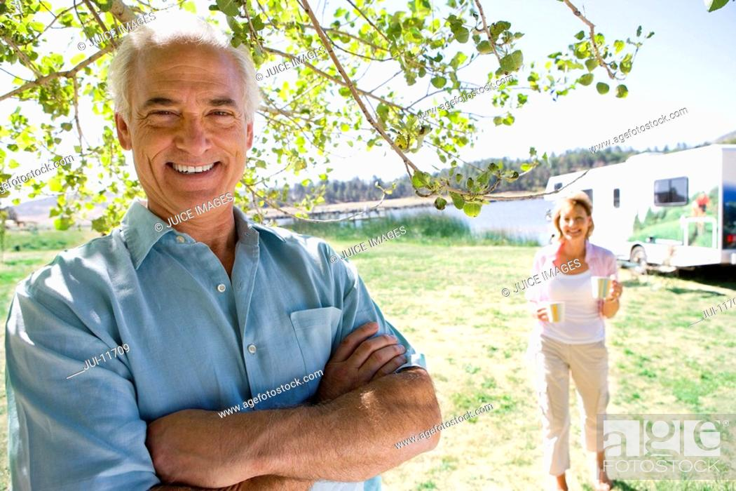Stock Photo: Mature man with arms crossed by wife and motor home outdoors, smiling, portrait.