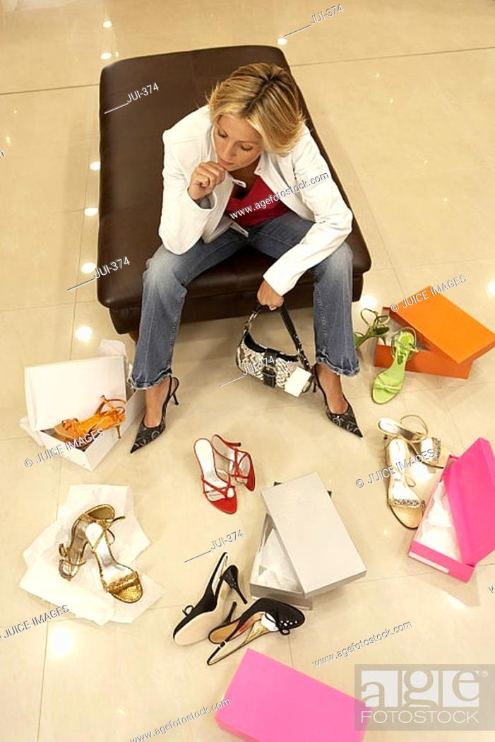 Stock Photo: Mature blonde woman trying on different pairs of high heels in shoe shop, hand on chin, thinking, elevated view.