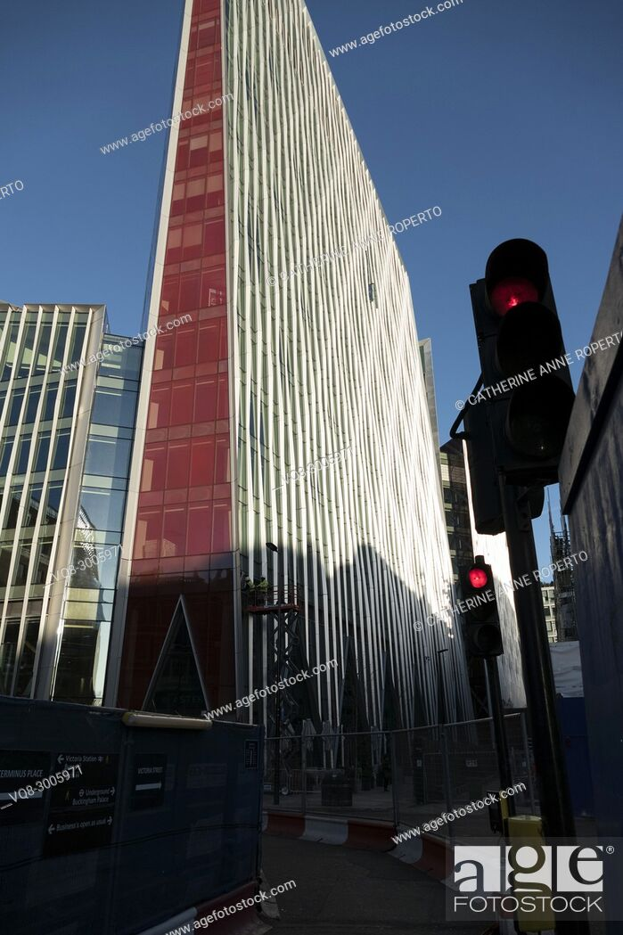 Imagen: Red and white shard-like contemporary architecture against a bright blue sky with red traffic lights and pedestrian barriers near Victoria tube station, London.