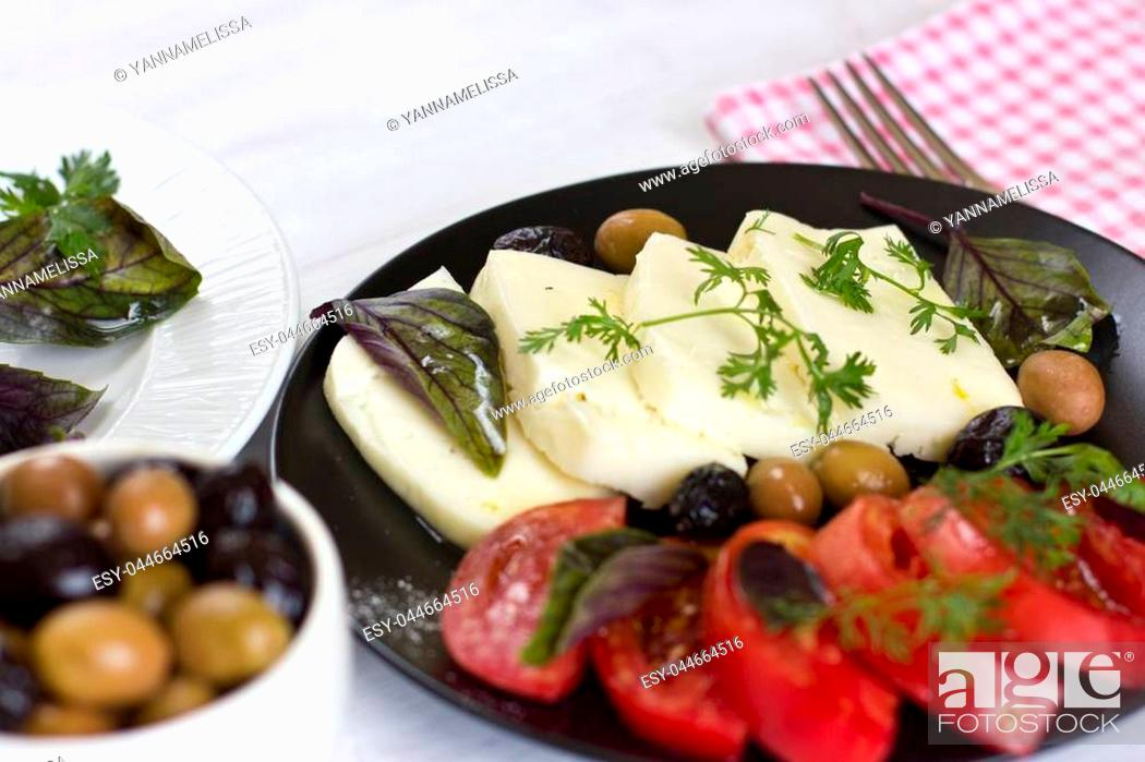 Stock Photo: White cheese with tomatoes, green and black olives, basil, coriander and olive oil on the black plate.