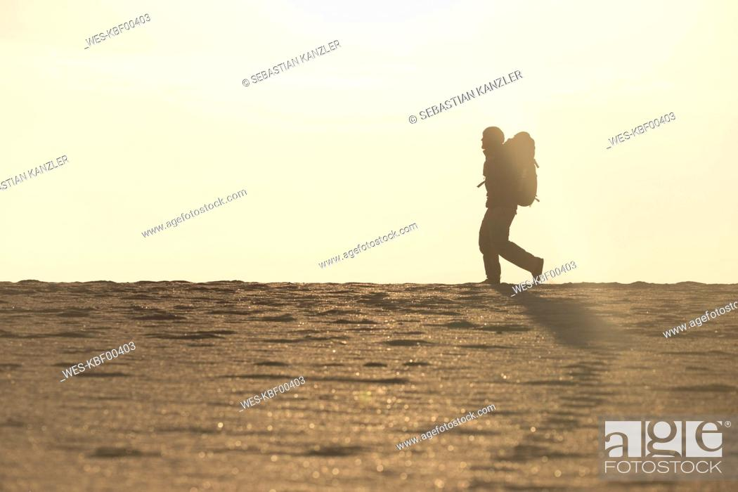 Photo de stock: Man with backpack at the beach in the evening light.