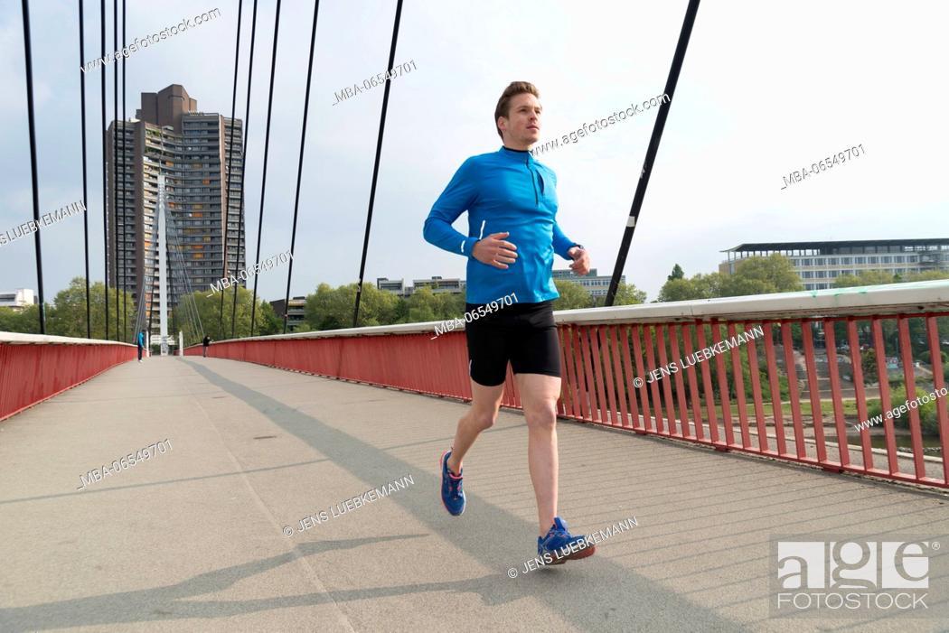 Stock Photo: Man with blue training shirt joging on a bridge.