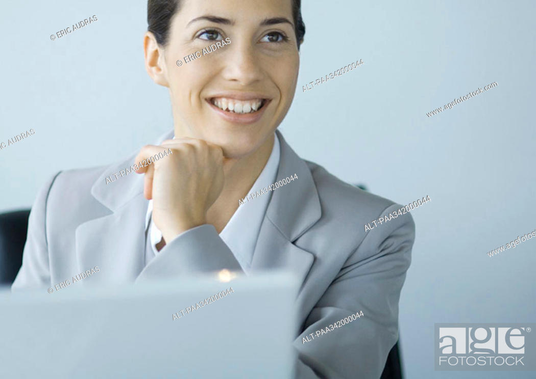Stock Photo: Businesswoman looking up from laptop.