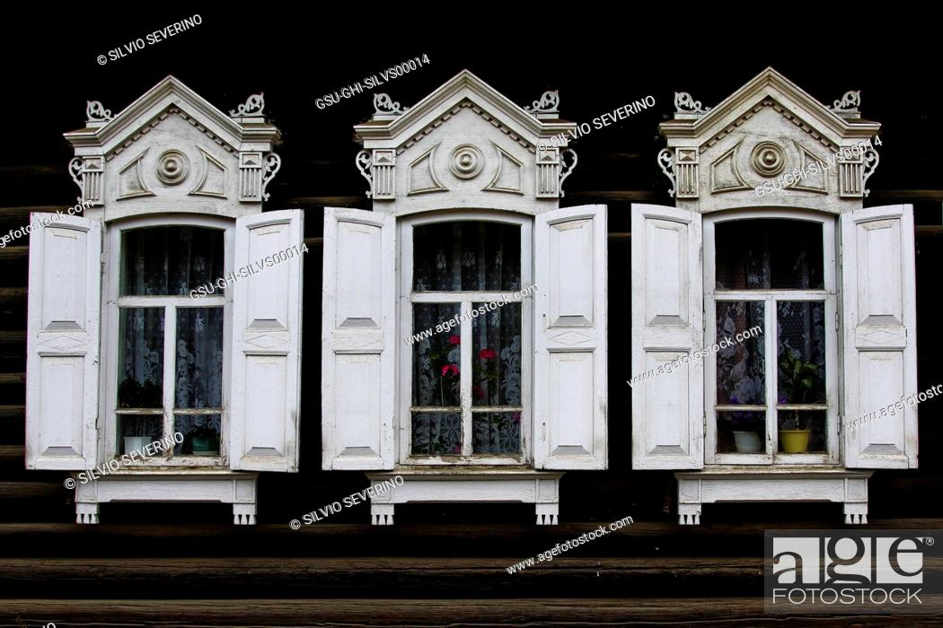 Stock Photo: Three Windows with White Shutters and Ornate Wood Detail.