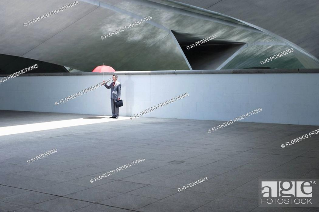 Stock Photo: Businessman standing outdoors on building holding umbrella.