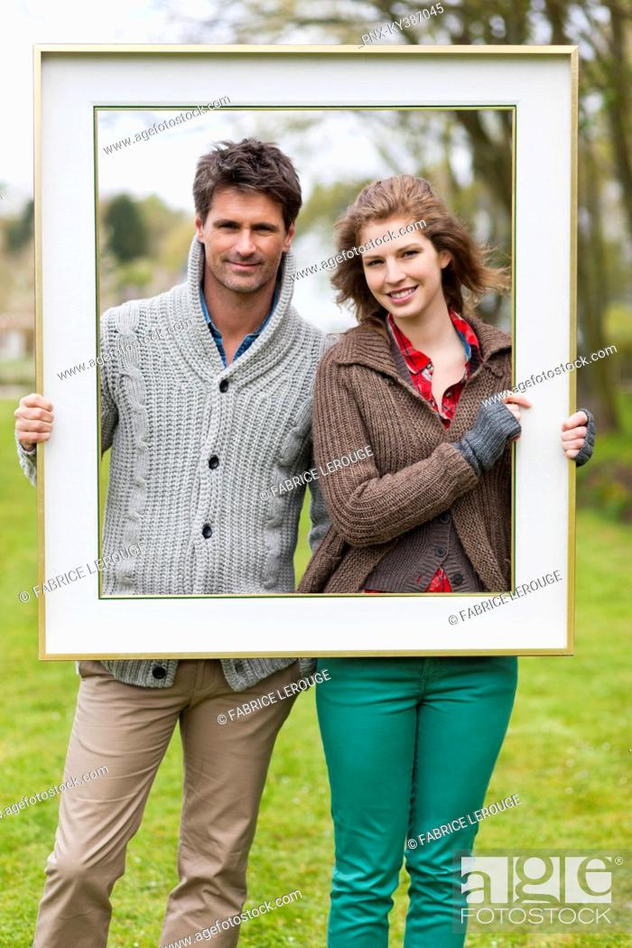 Stock Photo: Portrait of a couple holding a frame.