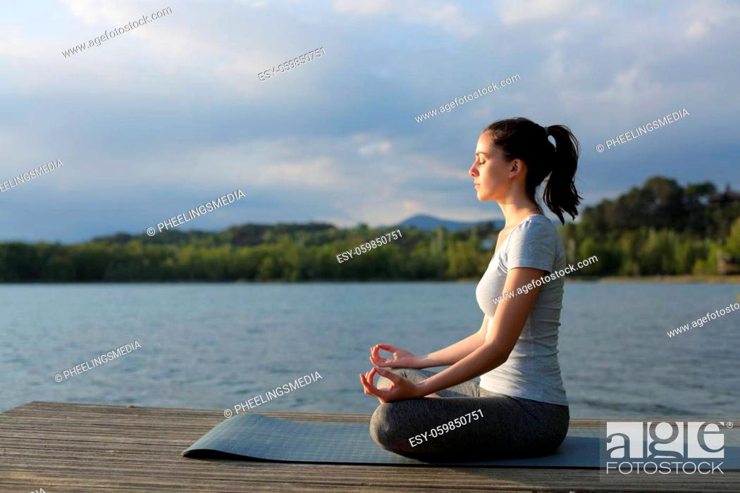 Stock Photo: Profile of a woman doing yoga exercise in a lake.