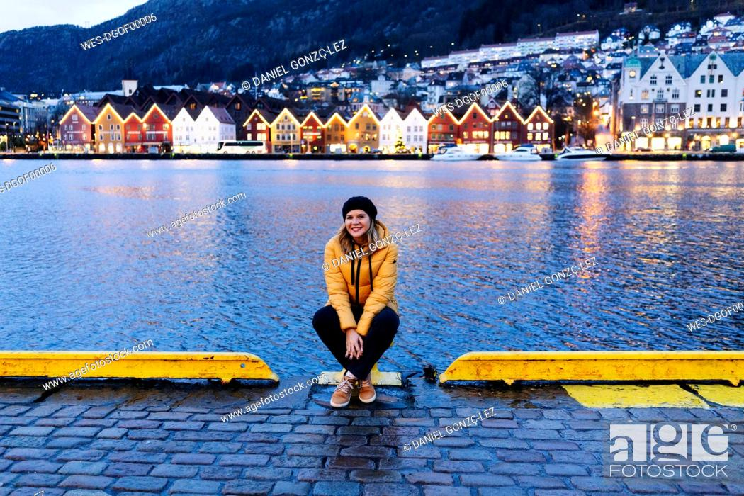 Imagen: Woman wearing a yellow jacket and sitting at harbour in Bergen, Norway.