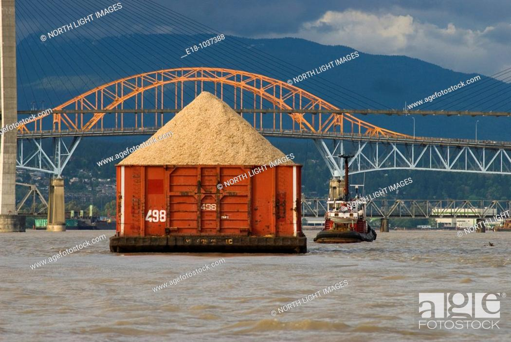 Stock Photo: Canada, BC, New Westminster  Load of wood chips being towed up the Fraser River  Patullo Bridge and Skytrain Bridge in background.