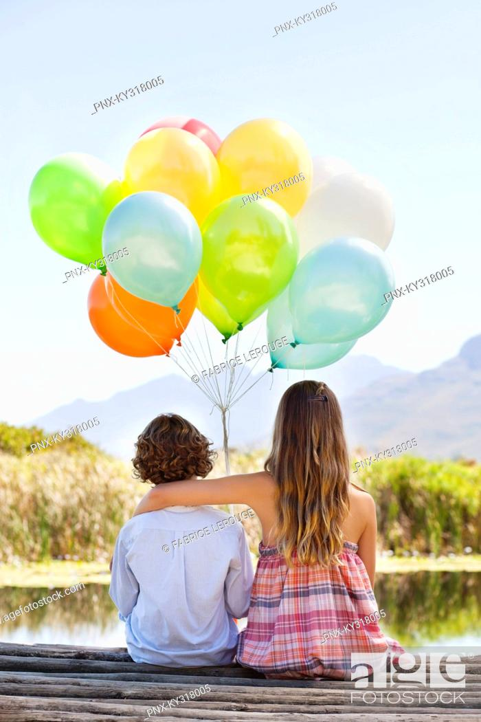 Stock Photo: Rear view of siblings playing with balloons at a pier.