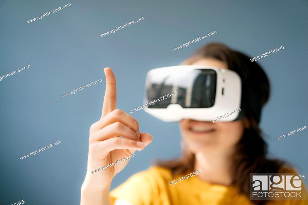Imagen: Woman wearing VR glasses, watching raised finger.