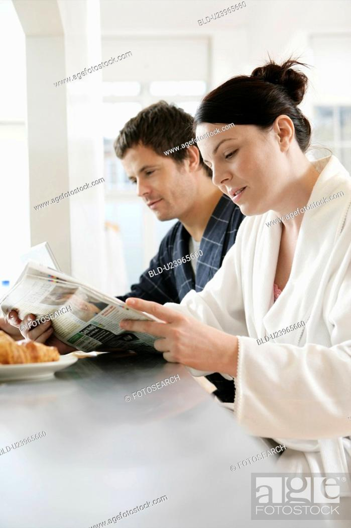 Stock Photo: Mid adult couple reading newspaper at breakfast.