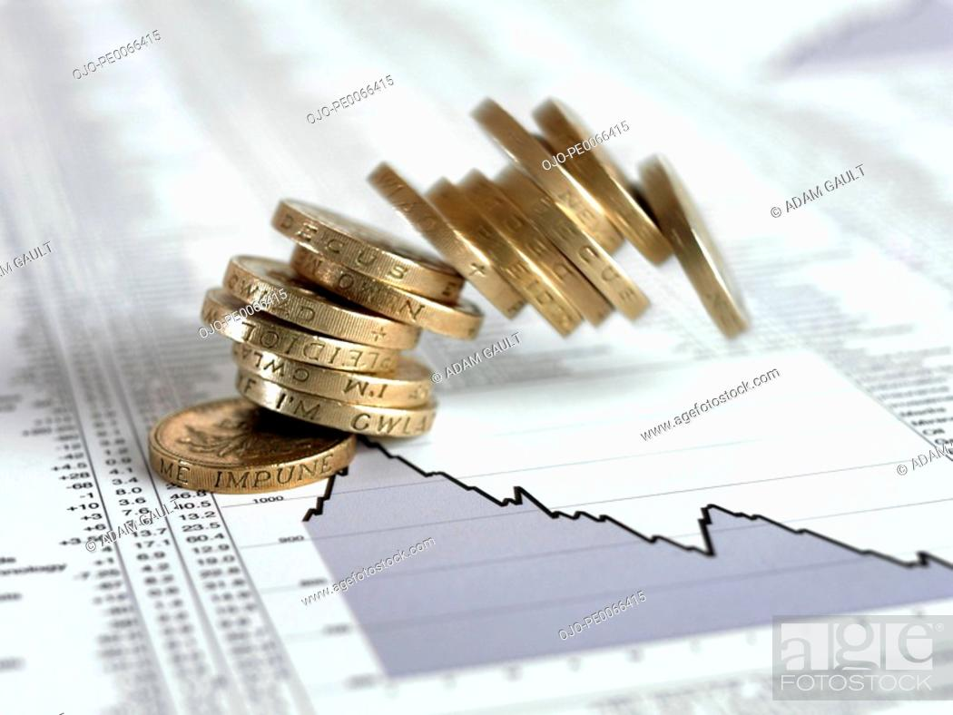 Stock Photo: Stack of British pound coins falling on list of share prices.