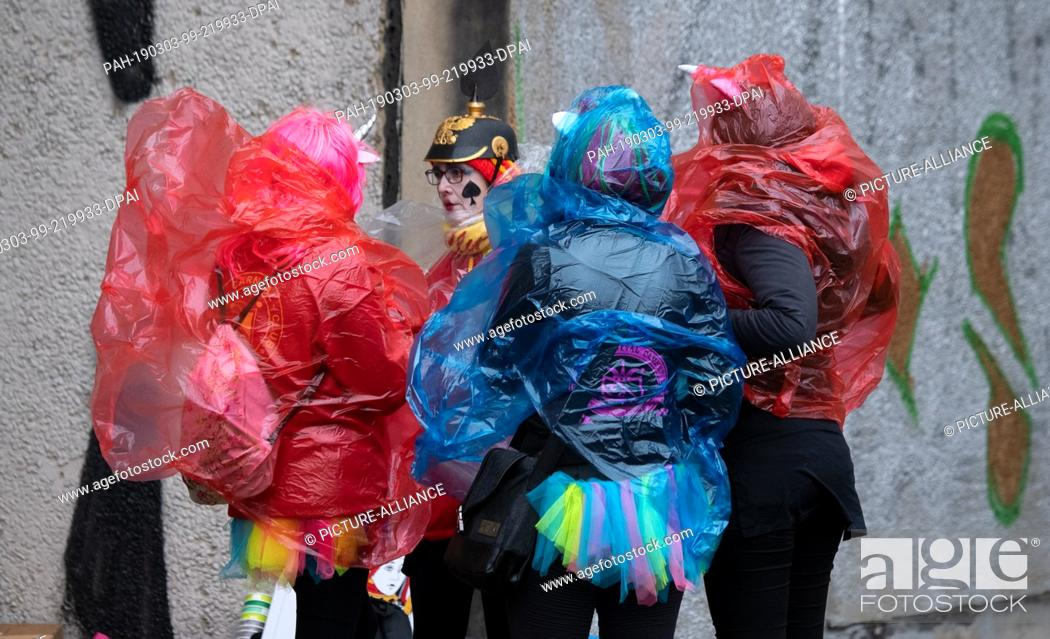 """Stock Photo: 03 March 2019, Brandenburg, Cottbus: Carnivalists in Cottbus protect themselves from the """"""""train of cheerful people"""""""" with foils from the rain."""