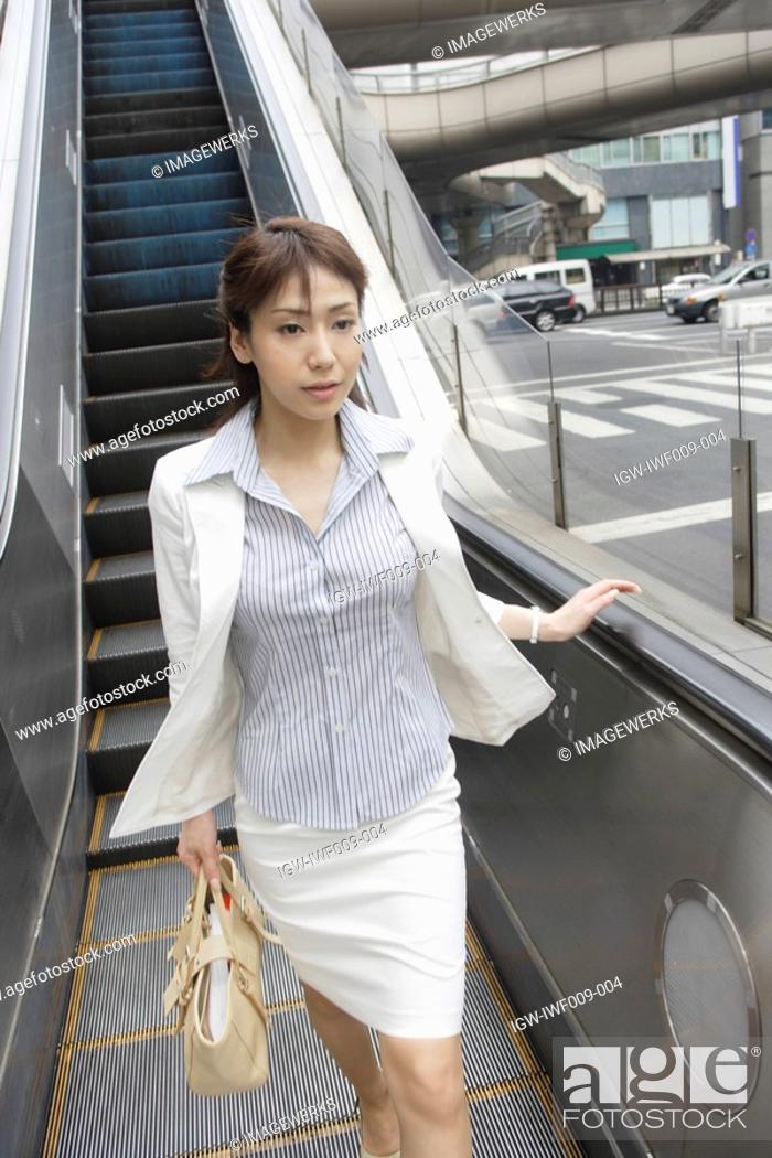 Stock Photo: A woman walking ahead after descending from the escalators.
