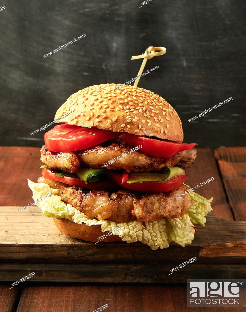 Stock Photo: hamburger with pork fried steak, red tomatoes, fresh round bun with sesame seeds on a vintage brown wooden board.