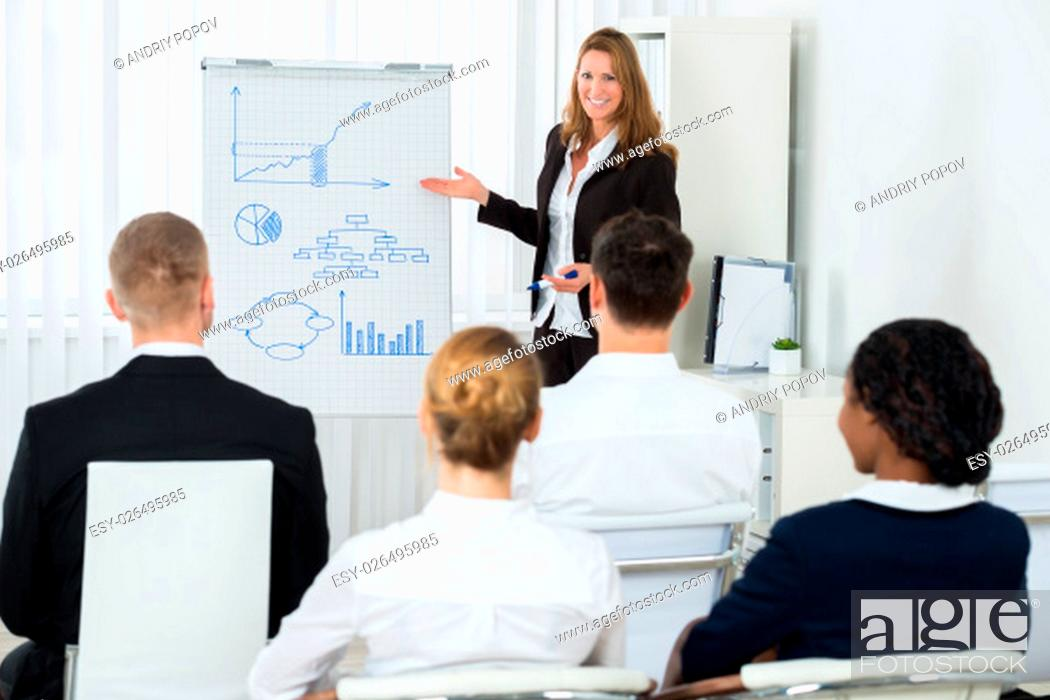 Stock Photo: Happy Female Manager Explaining Business Strategy To Her Team At Workplace.