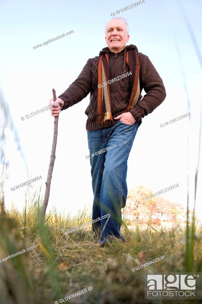 Stock Photo: Senior man hiking in a field.