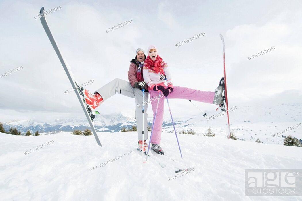 Stock Photo: Italy, South Tyrol, Seiseralm, Couple standing on skis, lifting leg.