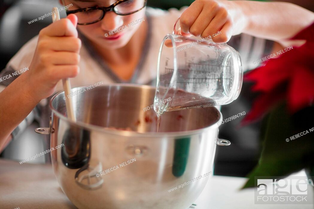 Stock Photo: Girl pouring egg white into mixing bowl for christmas cookies at kitchen counter, close up.