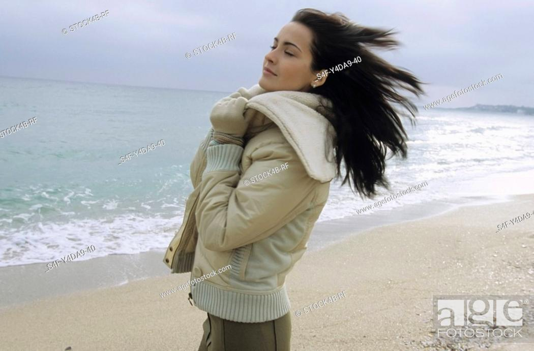 Stock Photo: Young darkhaired Woman cuddling herself into the Collar of her winterly Jacket - Wind - Season - Gesture - Beach.