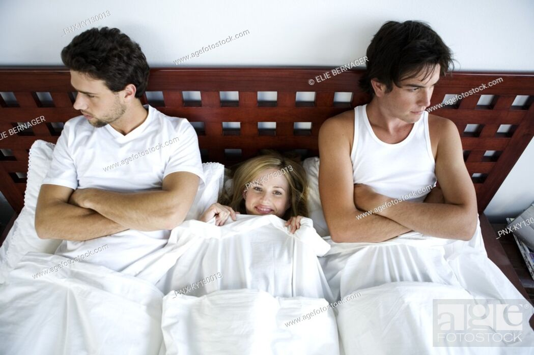 Stock Photo: Young smiling woman in bed between 2 men, arms crossed.